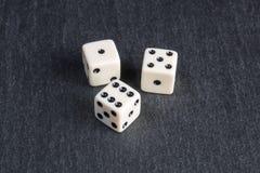 White dice. Small dice on dark stone background Stock Image