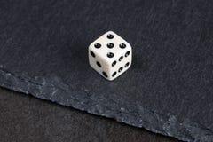 White dice. Small dice on dark stone background Stock Photo