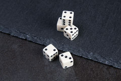 White dice. Small dice on dark stone background Royalty Free Stock Images