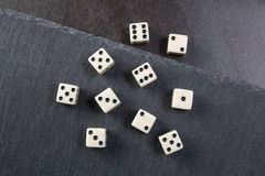 White dice. Small dice on dark stone background Stock Images