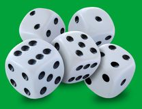 White dices in a pile thrown in a craps game, yatsy or any kind of dice game against a green background. Stock image stock image
