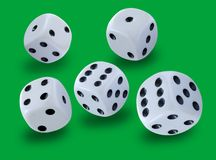 White dices thrown in a craps game, yatsy or any kind of dice game against a green background. Stock image royalty free stock image