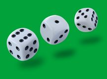 White dices thrown in a craps game, yatsy or any kind of dice game against a green background. Stock image stock photos