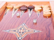White dices on wooden backgammon board isolated. Wooden handmade backgammon board with chips and two ivory dices on white background Stock Photo