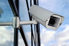 White Digital CCTV camera on the glass facade stock photo