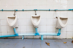 White dilapidated urinal on white wall Stock Photography