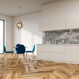 White dining room corner, blue chairs. White wall dining room and kitchen corner with a wooden floor, a round table and blue chairs. 3d rendering mock up Royalty Free Stock Photography