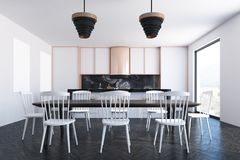 White dining room, poster, bookcases. White dining room interior with a wooden floor, a long table with white chairs near it, countertops and posters in the Royalty Free Stock Image