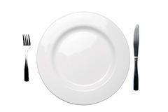 White dinner plate fork knife and clipping path. White empty dinner plate with fork and knife - clipping path included Royalty Free Stock Images