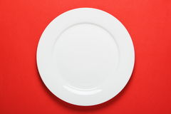 White Dinner Plate. A plain white dinner plate on a bright red paper background Royalty Free Stock Images