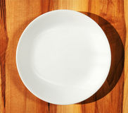 White dinner plate on wood table. Pure white porcelain dinner plate on kitchen hard wood table with shadow Royalty Free Stock Photo