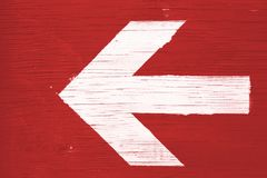 White arrow on red background: white directional arrow manually painted on a red wooden signboard. White directional arrow manually painted on a red wooden royalty free stock photos