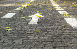 White directional arrow on stone pavement Royalty Free Stock Photo