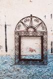 Ornate frame on a wall of a house. White dirty facade of a house with a light blue strctured base. Empty ornat iron rusted frame, giving a chance to a fantasy stock images