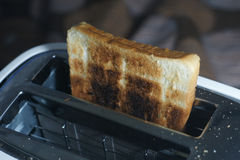 White dirty toaster and burned toast (selective focus,dark tone). White dirty toaster and burned toast (selective focus, dark tone Royalty Free Stock Photography