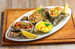 White dish with baked oyster shell cheese, salad oysters, served Stock Photos