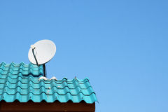 A white dish on the blue roof  Stock Photos