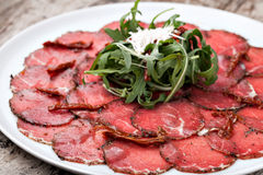 White dish with carpaccio of beef. On arugula royalty free stock images