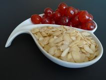 Almonds and Cherries. A white dish containing slivered almonds and glace cherries Royalty Free Stock Image