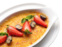 White dish with a cream brulee with raspberries, blueberries. Garnished with mint Stock Image