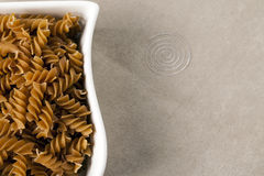 A white dish filled with uncooked wholewheat fusilli pasta. White dish filled with uncooked wholewheat fusilli pasta Royalty Free Stock Image