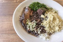 White dish with ingredients of brazilian feijoada. White dish with ingredients of feijoada, typical food of Brazil stock images