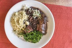 White dish with ingredients of brazilian feijoada. White dish with ingredients of feijoada, typical food of Brazil royalty free stock photo