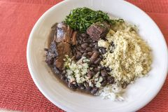 White dish with ingredients of brazilian feijoada. White dish with ingredients of feijoada, typical food of Brazil royalty free stock photos