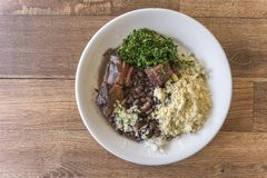 White dish with ingredients of brazilian feijoada. White dish with ingredients of feijoada, typical food of Brazil royalty free stock images