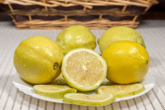 White dish with lemons with a wicker basket at background Royalty Free Stock Images