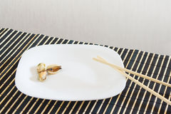 White dish with mussels and chopsticks Stock Photo