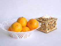 A white dish of oranges next to a box with a small decorative candle on it Royalty Free Stock Photos