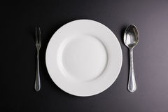 White dish, Spoon and fork  on black background with cop Stock Photography