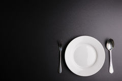 White dish, Spoon and fork  on black background with cop Stock Photos