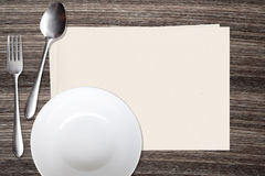White dish spoon fork and and paper on wood background Stock Photo