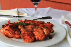 White dish with tender Chicken Cacciatore. Simple white plate with perfectly seasoned Chicken Cacciatore and glass of red wine at outdoor restaurant Royalty Free Stock Photography