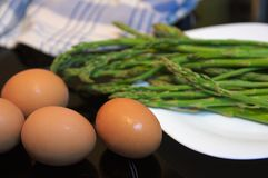 Green asparagus and brown eggs in a white dish. A white dish with three green asparagus and some brown eggs for the tortilla Stock Photography