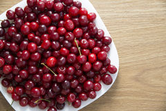 White dish up to the top filled with red ripe cherry Royalty Free Stock Photos