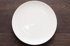 White dish on the wooden background. Top view royalty free stock images