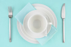 White dishes on aqua tablecloth. White dishes with knife and fork on aqua tablecloth Stock Photos