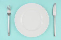 White dishes on aqua tablecloth. White dishes with knife and fork on aqua tablecloth Royalty Free Stock Image