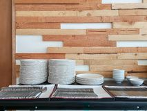 White dishes, ceramic bowls, fork and spoon on black table in front the horizontal line random pattern of brown pine wood royalty free stock photos