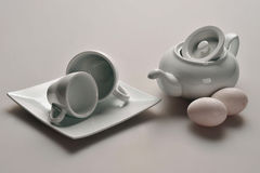 White dishes from Chinese porcelain: a teapot with a raised lid, two cups, saucer, next to the kettle lie two pink chicken eggs. Royalty Free Stock Photography