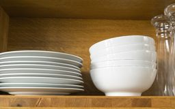 White dishes and glasses. In a kitchen shelf Royalty Free Stock Images