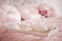White dishes on pink blanket, breakfast. Breakfast in bed with flowers and white cups on tray. Breakfast for Valentine`s day, concept of love. White dishes on royalty free stock photo