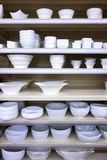 White dishes on shelves. White plate and dishes on shelves Royalty Free Stock Image