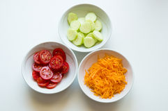 White dishes of tomatoes, carrots and cucumbers Royalty Free Stock Images