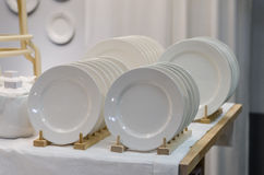 White dishes. Two rows of white dishes on the table royalty free stock photos