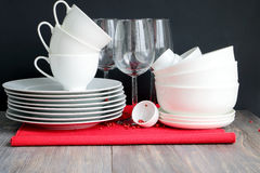 White dishware stacked on a wooden table against black background with transparent wineglasses Stock Photos