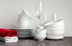 White dishware stacked on a wooden table against black background with transparent wineglasses Stock Images